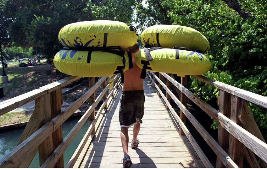 Nicholas Reese carries tubes for his friends across a bridge leading into a launch spot on the Comal