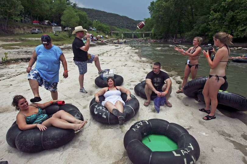Tubers relax on a rocky bank which would be submerged  if not for low water flow on the Guadalupe Ri