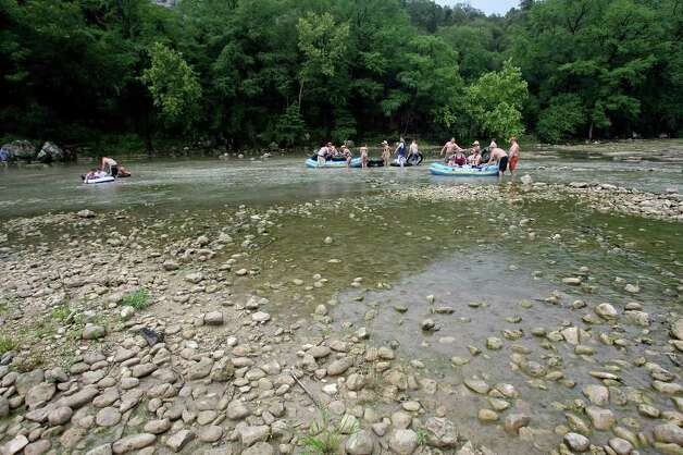 Tubers and boaters negotiate a low water level near the third crossing Saturday on the Guadalupe River.  Normal river flow rate would have the water moving over the top of these rocks.  May 23, 2009.   Tom Reel/Staff Photo: TOM REEL, Tom Reel/Express-News / treel@express-news.net