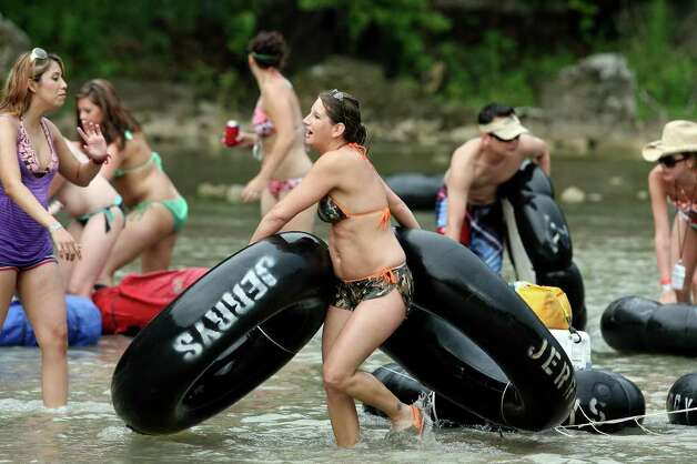 Tubers carry their tubes through a rocky area of the Guadalupe River Saturday after getting stuck due to low water level.   May 23, 2009.   Tom Reel/Staff Photo: TOM REEL, Tom Reel/Express-News / treel@express-news.net