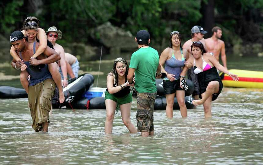 A group of recreationalists is force to walk over a rocky area on the Guadalupe River where their bo