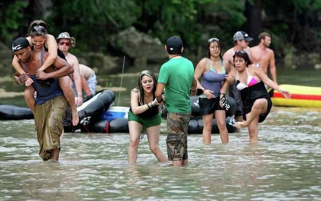 A group of recreationalists is force to walk over a rocky area on the Guadalupe River where their boat would not float due to low water level on Saturday.  May 23, 2009.   Tom Reel/Staff Photo: TOM REEL, Tom Reel/Express-News / treel@express-news.net