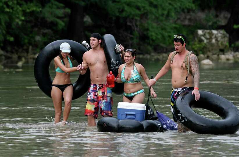 A group of tubers is forced to walk through a rocky area of the Guadalupe River near the third cross