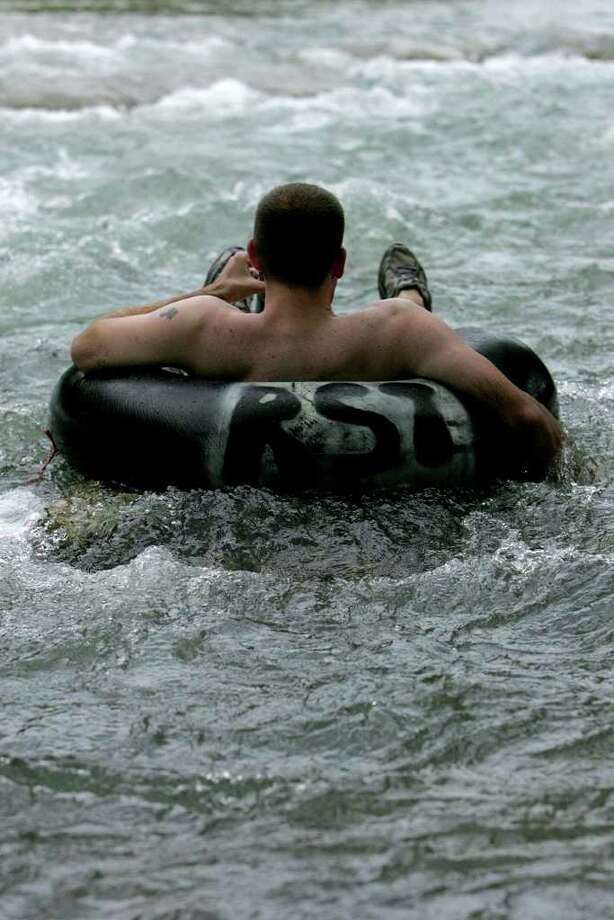 Joe Smith, from Cibolo, Texas drifts in his tube on the Guadalupe River. On Sunday July 6, 2008 people gathered at the Guadalupe River for tubing as an end to the long holiday weekend. Photo: MARIANA QUEVEDO, SAN ANTONIO EXPRESS-NEWS / © San Antonio Express-News