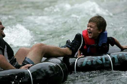 Father and son tube over the rapids on the Guadalupe River. On Sunday July 6, 2008 people gathered at the Guadalupe River for tubing as an end to the long holiday weekend. Photo: MARIANA QUEVEDO, SAN ANTONIO EXPRESS-NEWS / © San Antonio Express-News