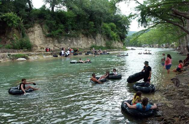 Recreationalists float slowly through the horseshoe loop of the Guadalupe River Saturday, June 28, 2003.    One year earlier, the river was over tree tops here and creating havoc all the way to the Gulf of Mexico.   Tom Reel/Staff. 