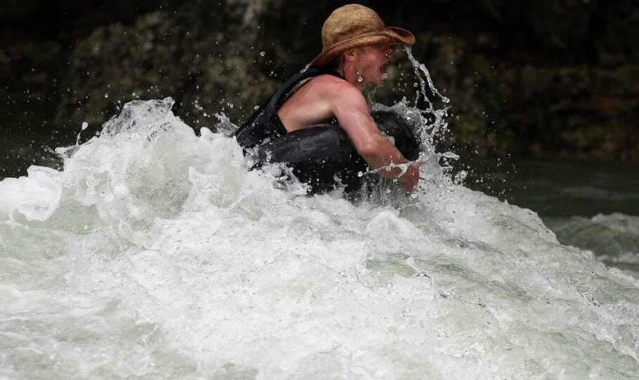 A tuber braves the high water and rapids on the Guadalupe River north of Gruene, Texas near River Ro