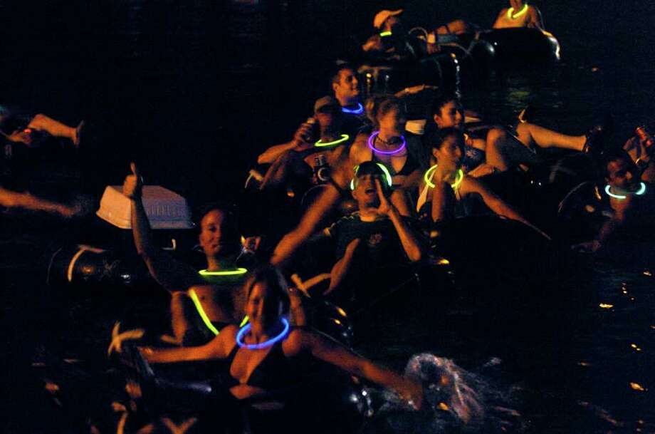 A group of night tubers revel in the fun of cruising down the Comal River in the dark Saturday night in New Braunfels. TOM REEL/STAFF   JUNE 17, 2006. Photo: TOM REEL, SAN ANTONIO EXPRESS-NEWS / SAN ANTONIO EXPRESS-NEWS