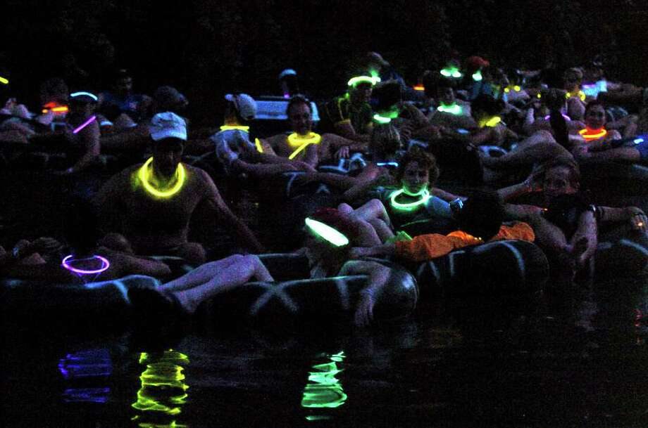 With lighted necklace glowing in the dark waters of the Comal River, Adventure Club members float together downstream from the Texas Tubes outfitter Saturday night. TOM REEL/STAFF   JUNE 17, 2006. Photo: TOM REEL, SAN ANTONIO EXPRESS-NEWS / SAN ANTONIO EXPRESS-NEWS
