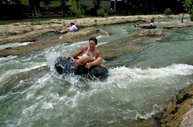 "METR O  A tuber thrills as she splashes into the white water of ""The Chute"" on the Guadalupe River north of New Braunfels Monday.   Traffic on the river was very light for a holiday.  Law officers on hand attribute the quite day to several nights of rain and thunderstorms.   TUBING ON THE GUADALUPE RIVER MAY 30, 2005  TOM REEL/STAFF Photo: TOM REEL, SAN ANTONIO EXPRESS-NEWS"