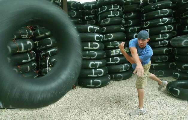METRO  Justin Malones heaves tubes toward the front of the store at Corner Tubes in New Braunfels Thursday.   Corner Tubes rents to recreationalists near the Comal River and Guadalupre River confluence .  AMY PRICE AND STEVE PRICE WITH KIDS ALSO TUBING PREPARATION ON GUADALUPE RIVER   TOM REEL/STAFF   MAY 26, 2005. Photo: TOM REEL, SAN ANTONIO EXPRESS-NEWS / San Antonio Express-News