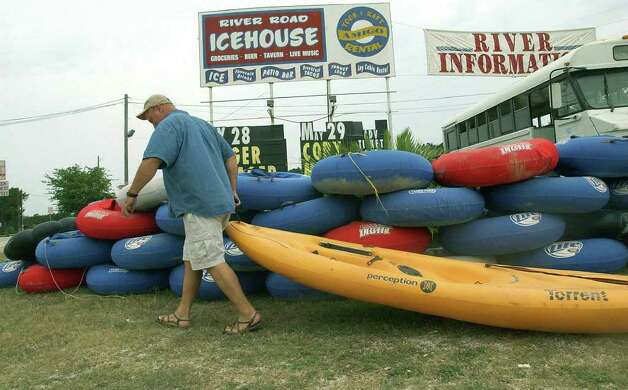 METRO  Mel Polk drags one of his canoes out for display at Amigo Mel's near Huaco Falls on the Guadalupe River above New Braunfels Thursday.   AMY PRICE AND STEVE PRICE WITH KIDS ALSO TUBING PREPARATION ON GUADALUPE RIVER   TOM REEL/STAFF   MAY 26, 2005. Photo: TOM REEL, SAN ANTONIO EXPRESS-NEWS / San Antonio Express-News