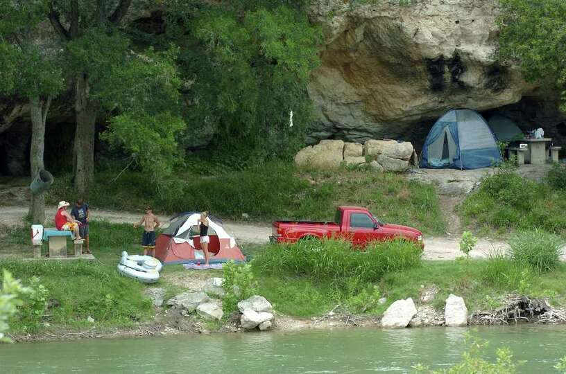 METRO  Campers set up on the banks of the Guadalupe, some of the tents going in to sheltering caves