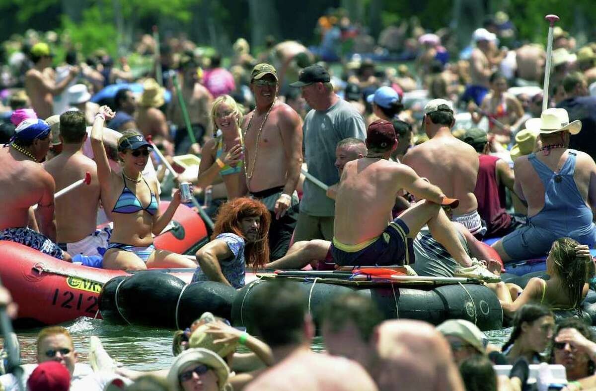 METRO River goers above Slumber Falls take advantage of the slow current before the rapids to keep the party going. TUBING ON THE GUADALUPE RIVER. TOM REEL/STAFF MAY 29, 2004.