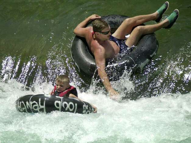 Tubers float the Comal River after it reopened in New Braunfels, Texas, Wednesday, July 24, 2002. Floating on the Comal and Guadalupe rivers was halted during the July 4th weekend after heavy rains caused flooding along both rivers. Most debris has been cleared from the Comal River, but the Guadalupe River remains closed to tubing. Photo: ERIC GAY, AP / AP