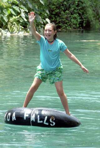 METRO    Parker Shea is all smiles as she stands on her tube in the Comal River Wednesday, July 24, 2002.  The ten year old was one of the first to hit the river after tubing restrictions were lifted.  Photo by Tom Reel/Staff Photo: TOM REEL ,  SAN ANTONIO EXPRESS-NEWS / SAN ANTONIO EXPRESS-NEWS