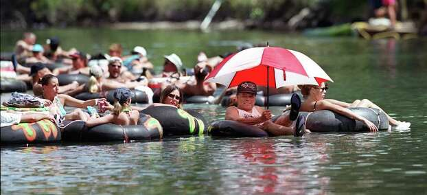 INSIGHT / ADVANCE / FOR 09 03 00 / FOR LINDA VAUGHAN:   Luis Ayala of ColLege Station, Texas beats the Labor Day weekend heat by shielding himself   from the sun with an umbrella and staying cool while tubing down the Guadalupe River Sunday Sept. 05, 1999 near Sattler, Texas. Ayala said he tries to make the river tri each Labor day holiday. Photo: JOHN DAVENPORT / EXPRESS-NEWS