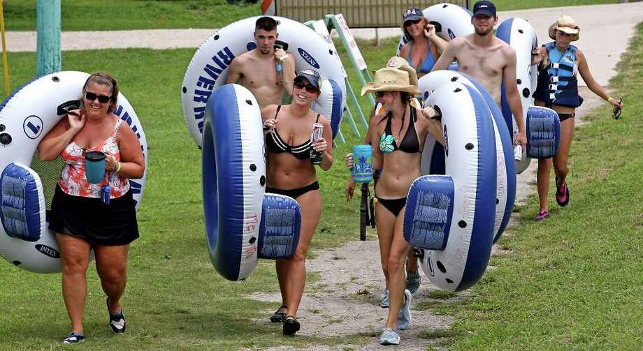 Joyce Casey (left) whose birthday is on the Fourth of July walks with Erin Casey (center) and Tiffany Richard toward the launching area for another floating trip on the horse shoe bend of the Guadalupe River near Sattler Friday.   The group is vacationing form Louisiana through the holiday.  Photo: TOM REEL, SAN ANTONIO EXPRESS-NEWS / SAN ANTONIO EXPRESS-NEWS