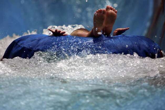 A young boy splashes along in one of the wild tube rides at the Schlitterbahn Water Park in New Braunfels, Friday, July 3, 2009. Jennifer Whitney/ jwhitney@express-news.net Photo: San Antonio Express-News / San Antonio Express-News