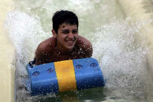 Frank Moreno, 13, from Dallas beats his brother to the bottom of the racing slide at the Schlitterbahn Water Park in New Braunfels, Friday, July 3, 2009. Jennifer Whitney/ jwhitney@express-news.net Photo: San Antonio Express-News / San Antonio Express-News