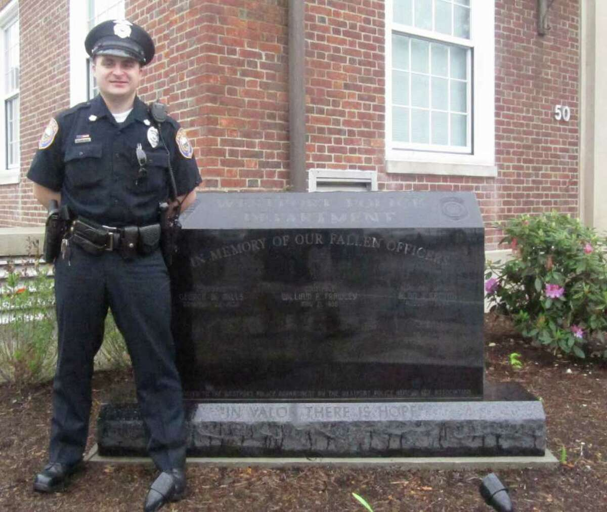 Westport Police Officer Casey Mezerewski stands by the new Westport Police Memorial in front of the Westport Police Department. The memorial pays tribute to the three men who have died in the line of duty while protecting and serving town residents. Casey's great-grandfather, Constable William Frawley, saw his life cut short at age 35 in 1936. The other two men on the memorial are Aldo Santini and George Mills.