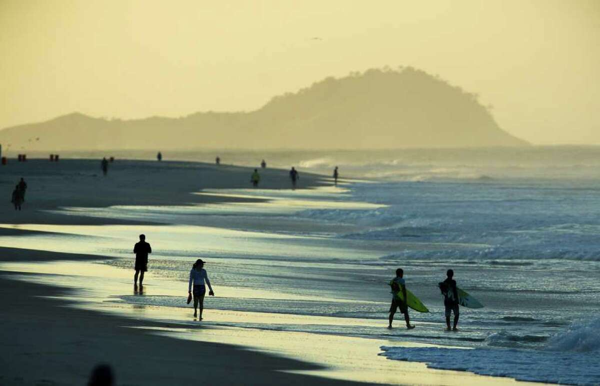 Surfers, right, walk at Barra de Tijuca beach where the Billabong Rio Pro surfing championship will take place in Rio de Janeiro, Brazil, Wednesday, May 11, 2011.