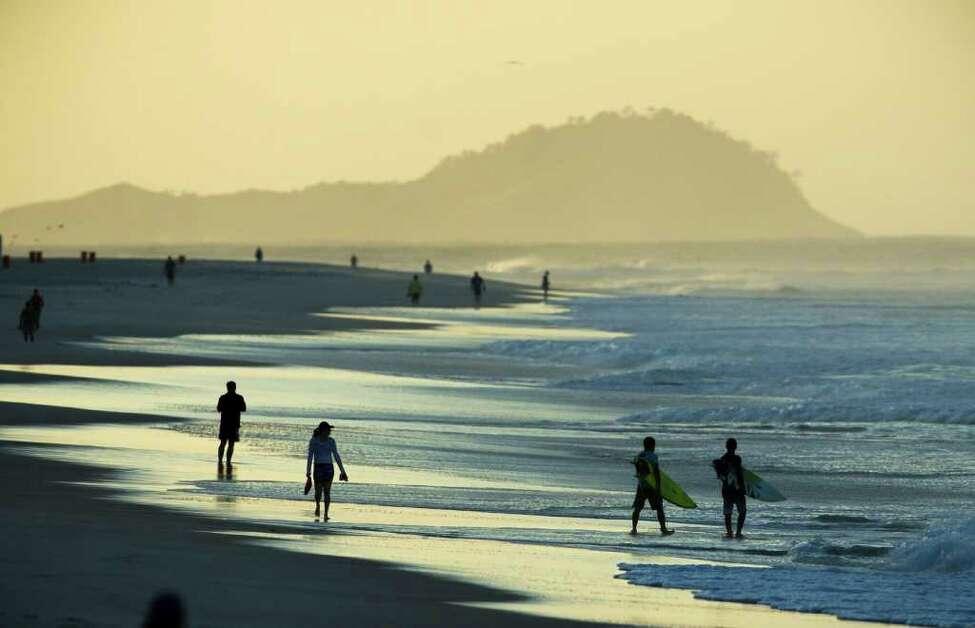 Surfers, right, walk at Barra de Tijuca beach where the Billabong Rio Pro surfing championship will take place in Rio de Janeiro, Brazil, Wednesday, May 11, 2011.