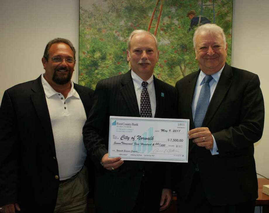 Norwalk Recreation and Parks Dept. Director Michael Mocciae, left, and Norwalk Mayor Richard Moccia receive a $7,000 check from First County Bank President Rey Giallango in support of the city's Summer Concert Series. Photo: Contributed Photo / Norwalk Citizen
