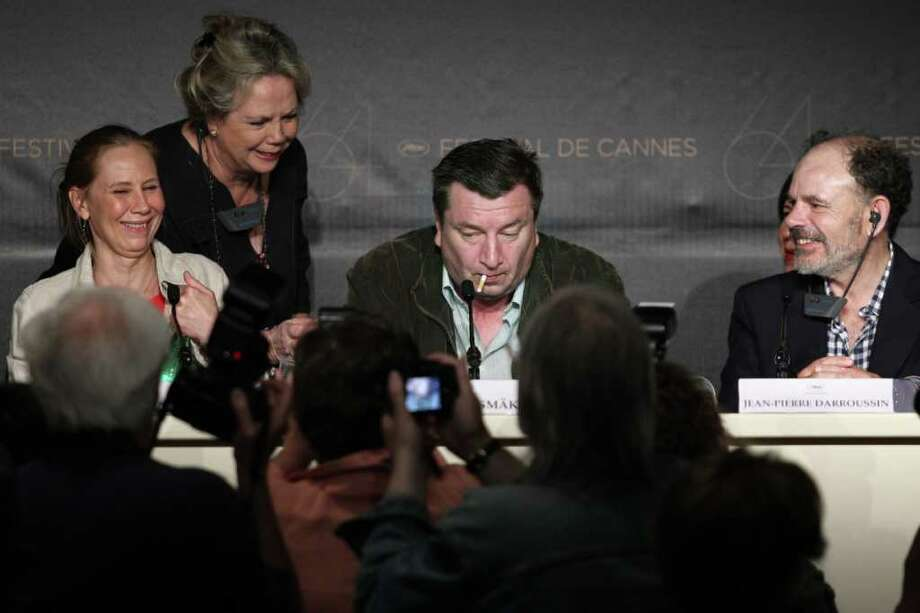 "Finnish director Aki Kaurismaki (C) puts a lit cigarette inside his mouth next to French actor Jean-Pierre Darroussin (R) and Finnish actress Kati Outinen as they attend the press conference of ""Le Havre"" presented in competition at the 64th Cannes Film Festival on Tuesday in Cannes.   AFP PHOTO / GUILLAUME BAPTISTE Photo: GUILLAUME BAPTISTE, AFP/Getty Images / 2011 AFP"