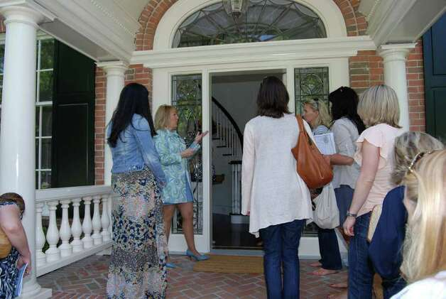 New Canaan CARES Executive Director Meg Domino meets and greets tourgoers at the home on Brushy Ridge. Photo: Jeanna Petersen Shepard / New Canaan News