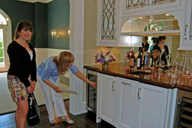 Judy Larson of Gardiner and Larson Homes shows Christie Hartnett some design aspects of the newly built bar area at the Brushy Ridge home. Photo: Jeanna Petersen Shepard / New Canaan News