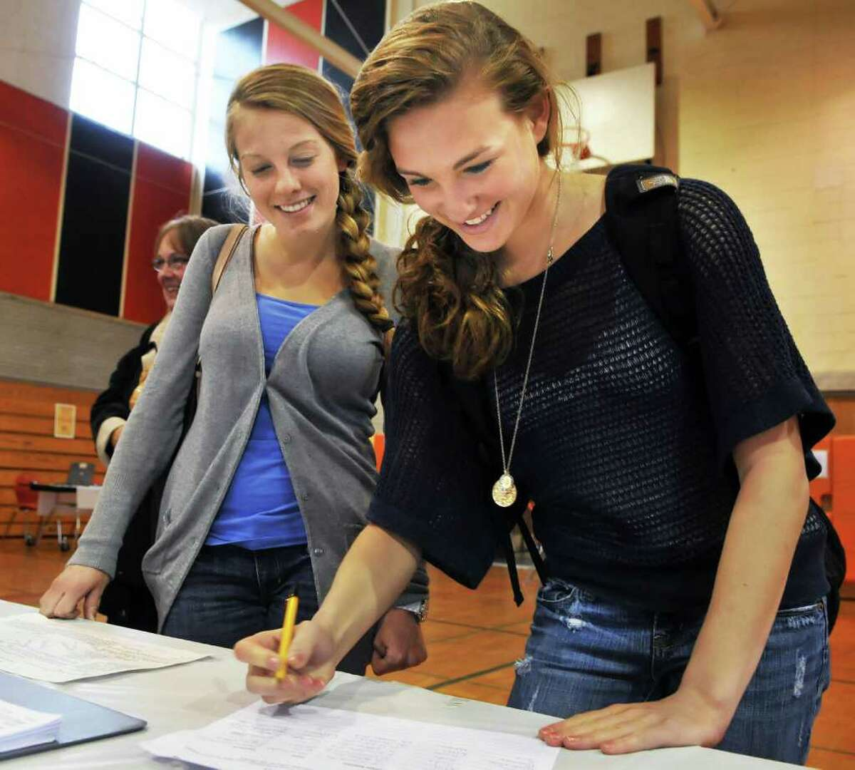First-time voters Veronica Lane, left, and Megan Perry sign in for Bethlehem High School's budget vote on Tuesday, May 17, 2011. (John Carl D'Annibale / Times Union)