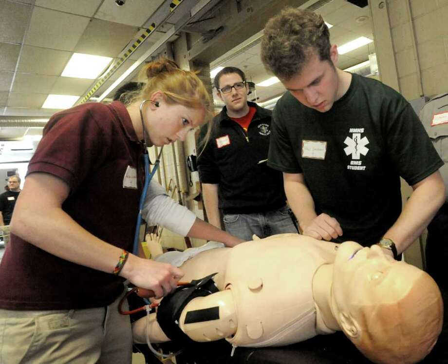 Alexa Witcofsky, 17, of Bethel High School, left, and Philip Jackson, 18, of New Milford High School, right, are evaluated by Dylan Kelleher, center, as they treat a mock victim during the EMT Olympics held at the Bethel Volunteer Fire Department, Tuesday, May 17, 2011. Photo: Michael Duffy / The News-Times