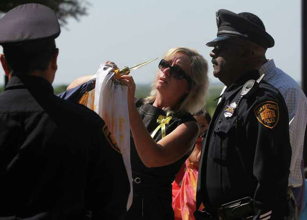 Shawn Brown (center)places a ribbon in tribute to her daughter Stephanie Brown on the San Antonio Police Memorial Flag during a tribute ceremony to fallen San Antonio Police Officers at the police Training Academy Tuesday May 17, 2011. On the right is Stephanie Brown's father Stanley Brown. Stephanie Brown was killed in a car accident while on duty last March. JOHN DAVENPORT/jdavenport@express-news
