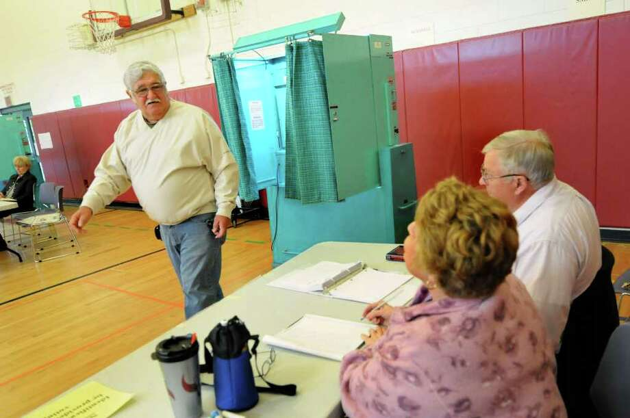 After voting, Richard Poulopoulos of Albany, left, chats with election inspectors Carol Carpenter and John Deyoe on Tuesday, May 17, 2011, at Eagle Point Elementary in Albany, N.Y. (Cindy Schultz / Times Union) Photo: Cindy Schultz