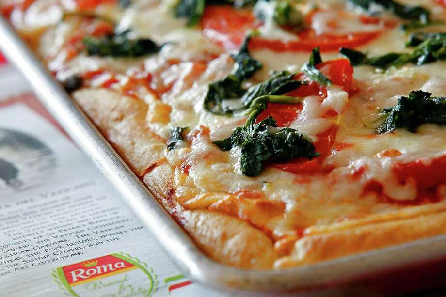 Sicilian pizza, has a thick, bready crust, a square shape and a layer of tomato sauce that soaks into the crust just a little. Photo: JERRY LARA, San Antonio Express-News / SAN ANTONIO EXPRESS-NEWS