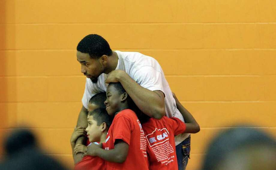 Spurs' Da'Sean Butler hugs a group of kids while they pose for a photo at the East Side Branch Boys and Girls Club on Tuesday, May 17, 2011. Butler was joined by teammates James Anderson and Danny Green. The trio met and played games with the kids during their visit. Photo: Kin Man Hui/Express-News / San Antonio Express-News