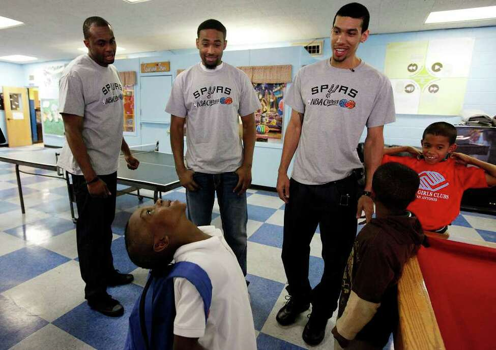 Spurs players James Anderson (from left), Da'Sean Butler and Danny Green ask a playful Chris Taylor (bottom left) questions during their visit with kids at the East Side Branch Boys and Girls Club on Tuesday, May 17, 2011. The trio met and played games with the kids during their visit.