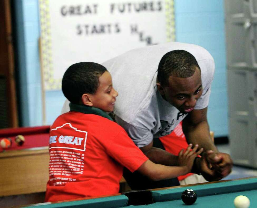 Spurs player James Anderson (right) kids around with Jaylen Sanchez during a game of billiards at the East Side Branch Boys and Girls Club on Tuesday, May 17, 2011. Anderson was joined by teammates Danny Green and Da'Sean Butler. The trio met and played games with the kids during their visit.
