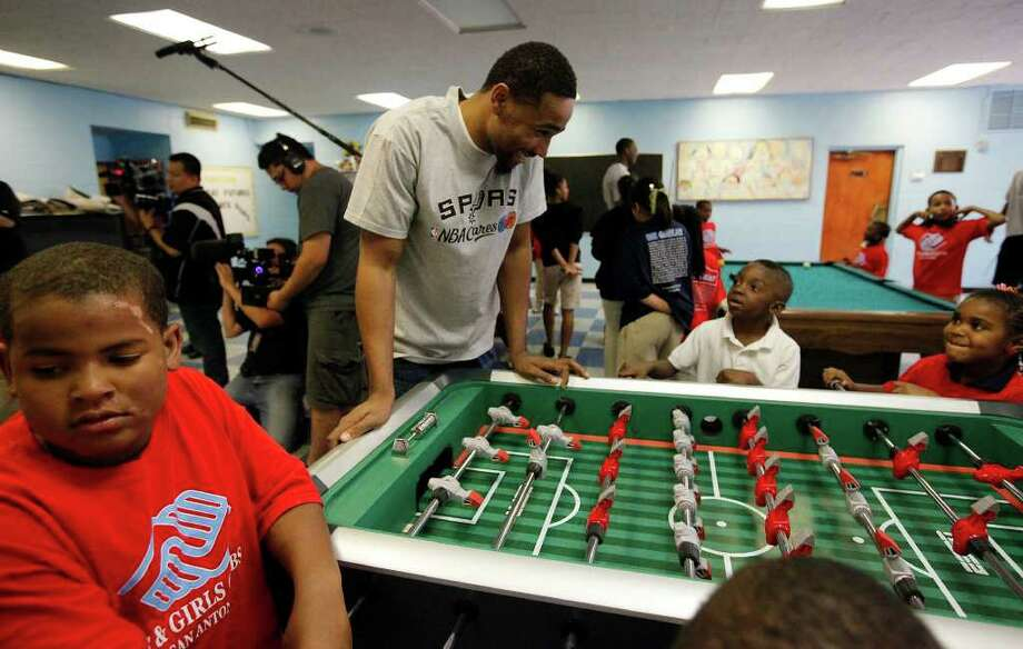 Spurs player Da'Sean Butler smiles as he watches kids play foosball at the East Side Branch Boys and Girls Club on Tuesday, May 17, 2011. Butler was joined by teammates James Anderson and Danny Green. The trio met and played games with the kids during their visit. Photo: Kin Man Hui/Express-News / San Antonio Express-News
