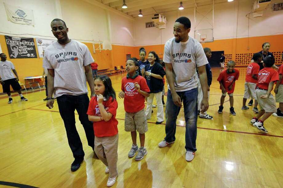 Spurs players James Anderson (left) and Da'Sean Butler share a laugh as kids play basketball at the East Side Branch Boys and Girls Club on Tuesday, May 17, 2011. Anderson and Butler were joined by teammate Danny Green. The trio met and played games with the kids during their visit. Photo: Kin Man Hui/Express-News / San Antonio Express-News