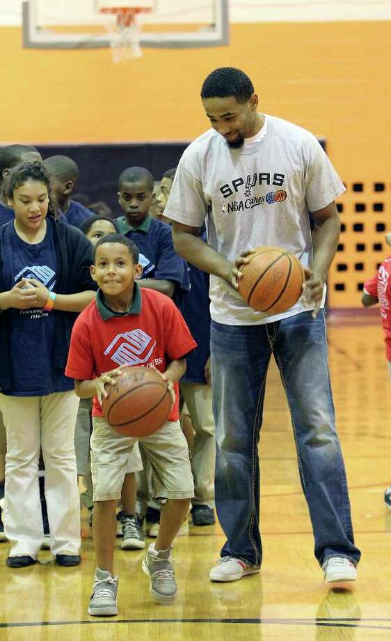 Spurs player Da'Sean Butler watches kids shoot basketballs during a visit at the East Side Branch Boys and Girls Club on Tuesday, May 17, 2011. Butler was joined by teammates James Anderson and Danny Green. The trio met and played games with the kids during their visit. Photo: Kin Man Hui/Express-News / San Antonio Express-News
