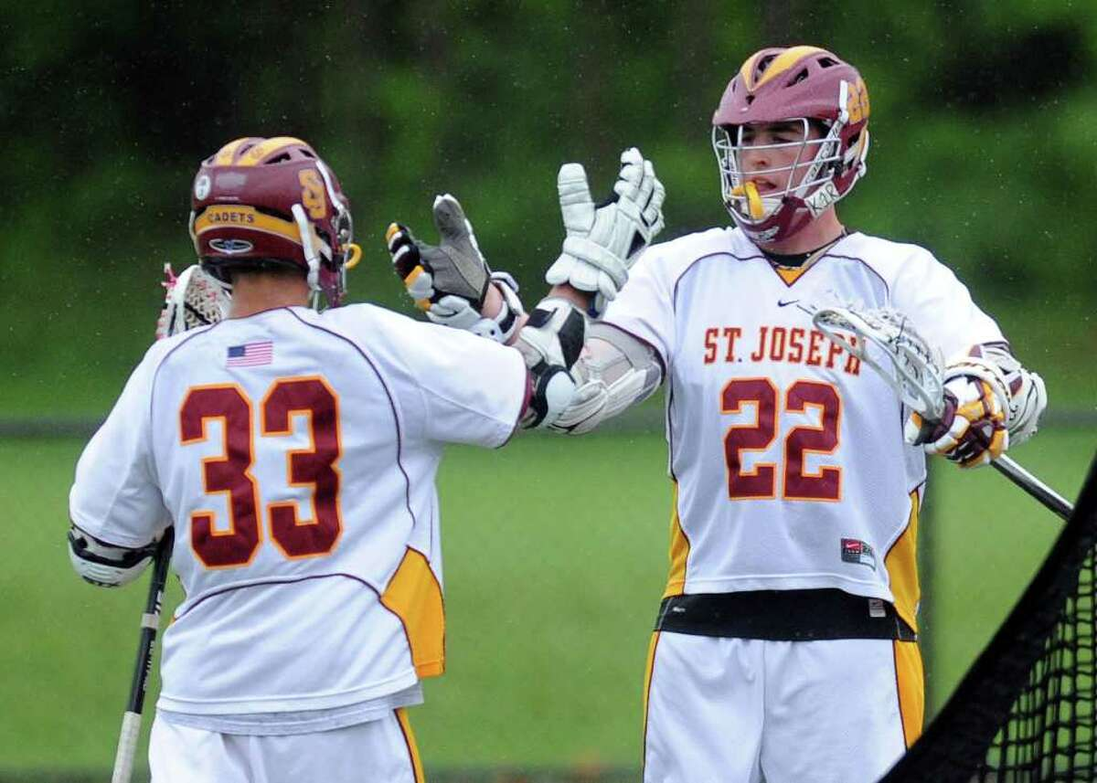 St. Joseph's Brian Bacarella and Mike Marini exchange a high-five after a goal during Tuesday's lacrosse game at St. Joseph High School on May 17, 2011.