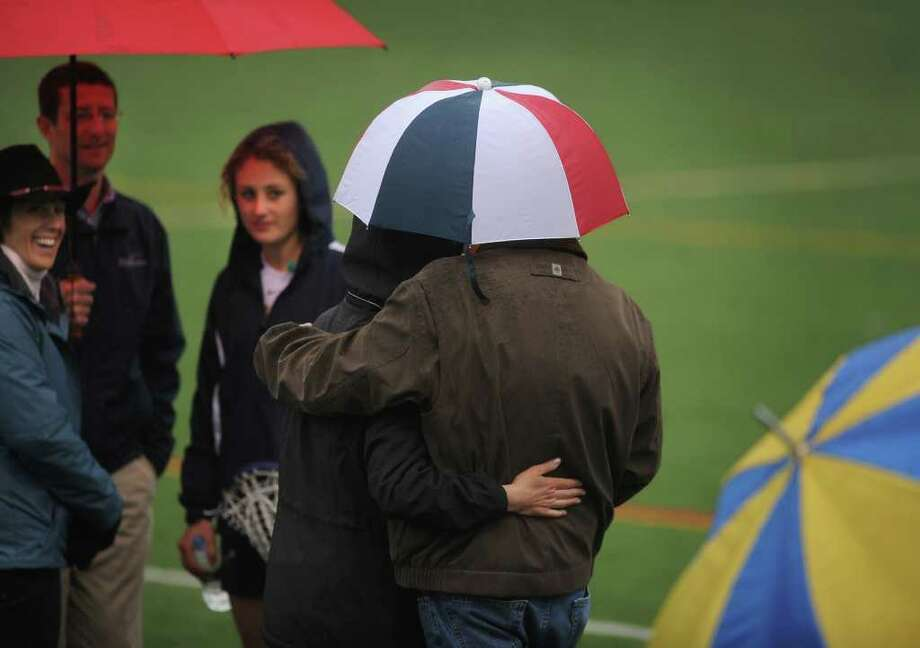 A couple share a very small umbrella as they watch a girls lacrosse game from the sidelines at Weston High School in Weston on Monday, May 16, 2011. Photo: Brian A. Pounds / Connecticut Post