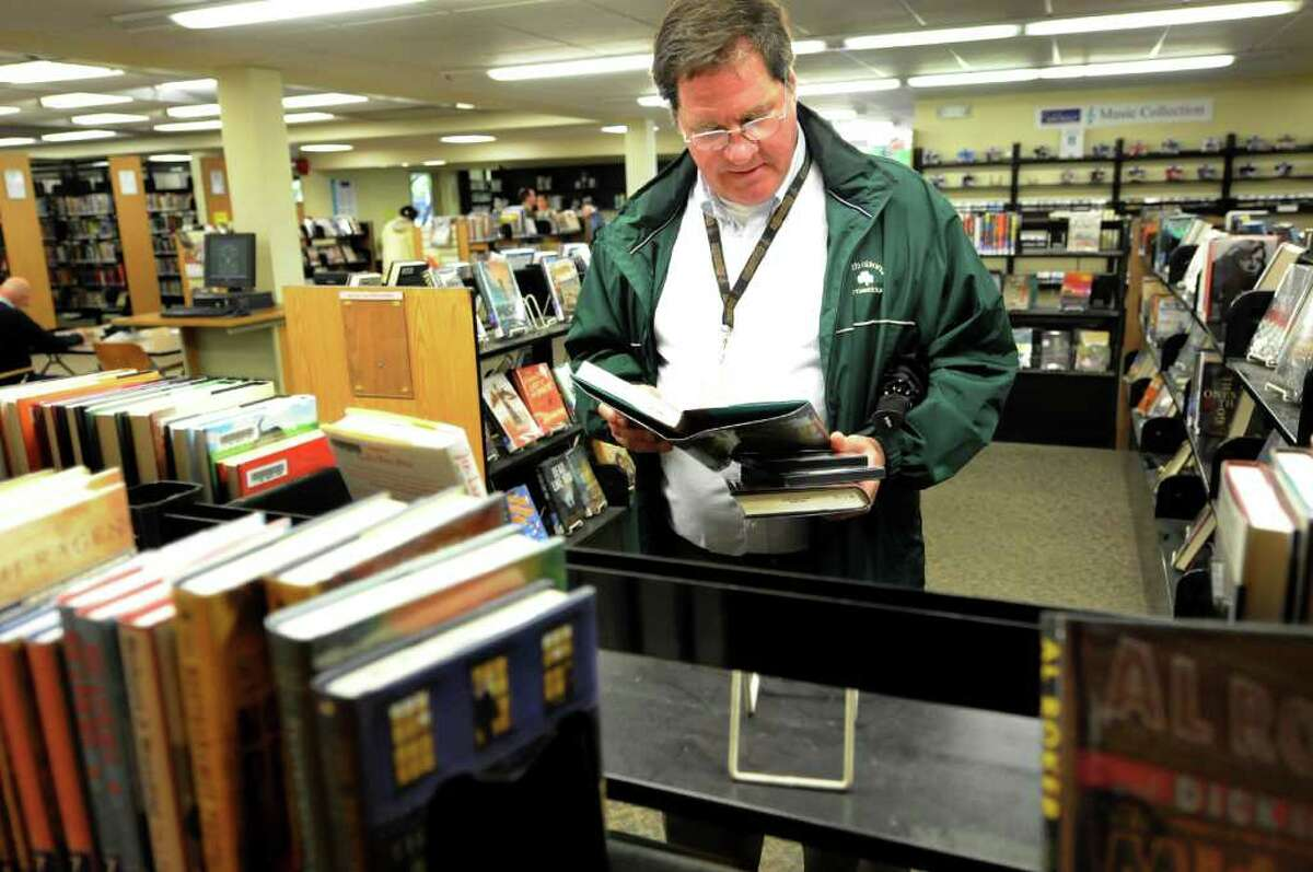 """Bruce Christie of Albany selects books to check out on Tuesday, May 17, 2011, at the Albany Public Library in Albany, N.Y. Because he uses its services, Christie said he'll vote """"yes"""" to support the Albany libraries. (Cindy Schultz / Times Union)"""