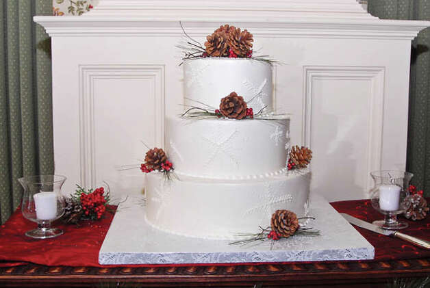 Their three-tiered wedding cake was decorated with snowflakes made of butter cream frosting, festooned with a wreath. (Photo by Joan Heffler) Photo: Joan Heffler