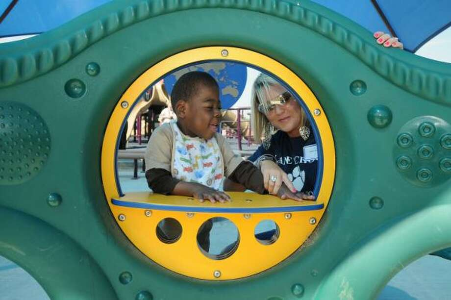 Robert Wilson, 4, left, from the Lane School in Aldine, and his teacher, Aimee Kerr of Spring, explore the LaFargue Learning Center at Lindsay/Lyons Park in Humble during the dedication of the newest addition to the Be An Angel Playground. Photo by Jerry Baker Photo: Jerry Baker, For The Chronicle