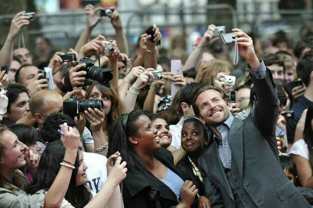 "US actor Bradley Cooper takes a picture of himself with fans on his arrival for the UK Premiere of the film '""The A Team"" in Leicester Square, central London, on July 27, 2010.  (Carl Court/AFP/Getty Images) Photo: CARL COURT / AFP"