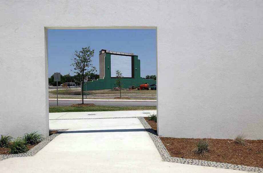 METRO -- The former Mission Drive-In movie screen is visible through the openings of the South Courtyard of the newly-opened Mission Branch Library, Tuesday, May 17, 2011. JERRY LARA/glara@express-news.net Photo: JERRY LARA, San Antonio Express-News / SAN ANTONIO EXPRESS-NEWS