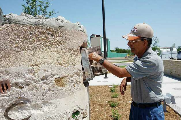 "METRO --Rudy Valero checks out a piece of artwork by Chris Sauter entitled, ""Core Samples (projector), 2011"", made of layered concete with embeded artifacts, by the main entrance of the newly-opened Mission Branch Library, Tuesday, May 17, 2011. JERRY LARA/glara@express-news.net Photo: JERRY LARA, San Antonio Express-News / SAN ANTONIO EXPRESS-NEWS"